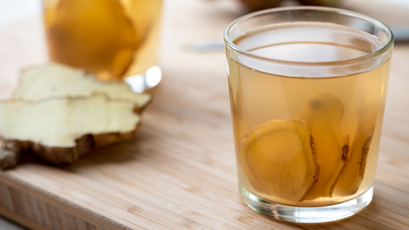 water glass on top of wood table with slices of ginger inside