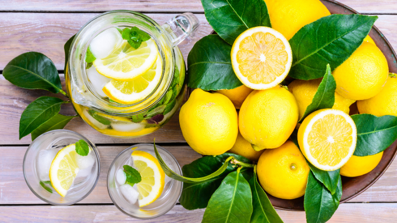 bowl of lemons next to pitcher and glasses of lemon water sitting on top of wood table