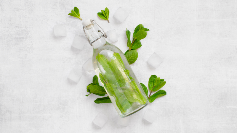 glass water bottle with mint leaves inside and around on top of table