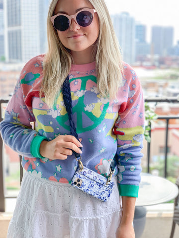 Nicole Miller Peace Sign Sweater with Blue Floral iPhone Case with woven camera crossbody bag strap