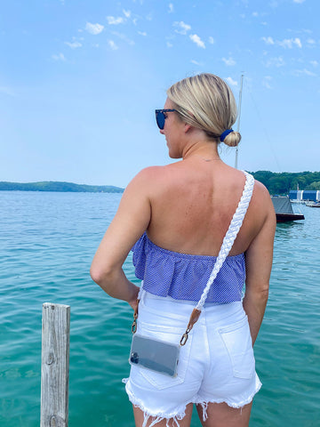 Girl on a boat dock on a lake in Michigan with an iPhone case and nautical rope crossbody strap.