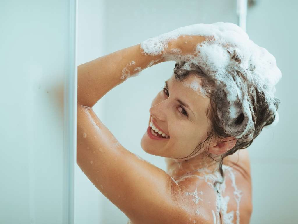 Bad shampoo ingredients woman using sulfates in the shower
