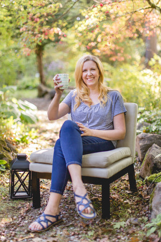 smiling woman holding cup of tea sitting in a garden