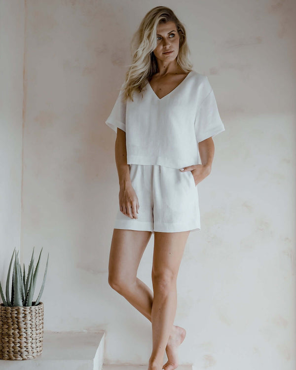 A woman wearing white linen blouse Molly, with short sleeves and V-neckline and and white linen shorts