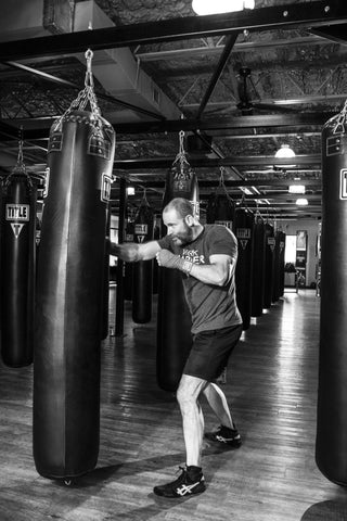 punching heavy bag with handwraps