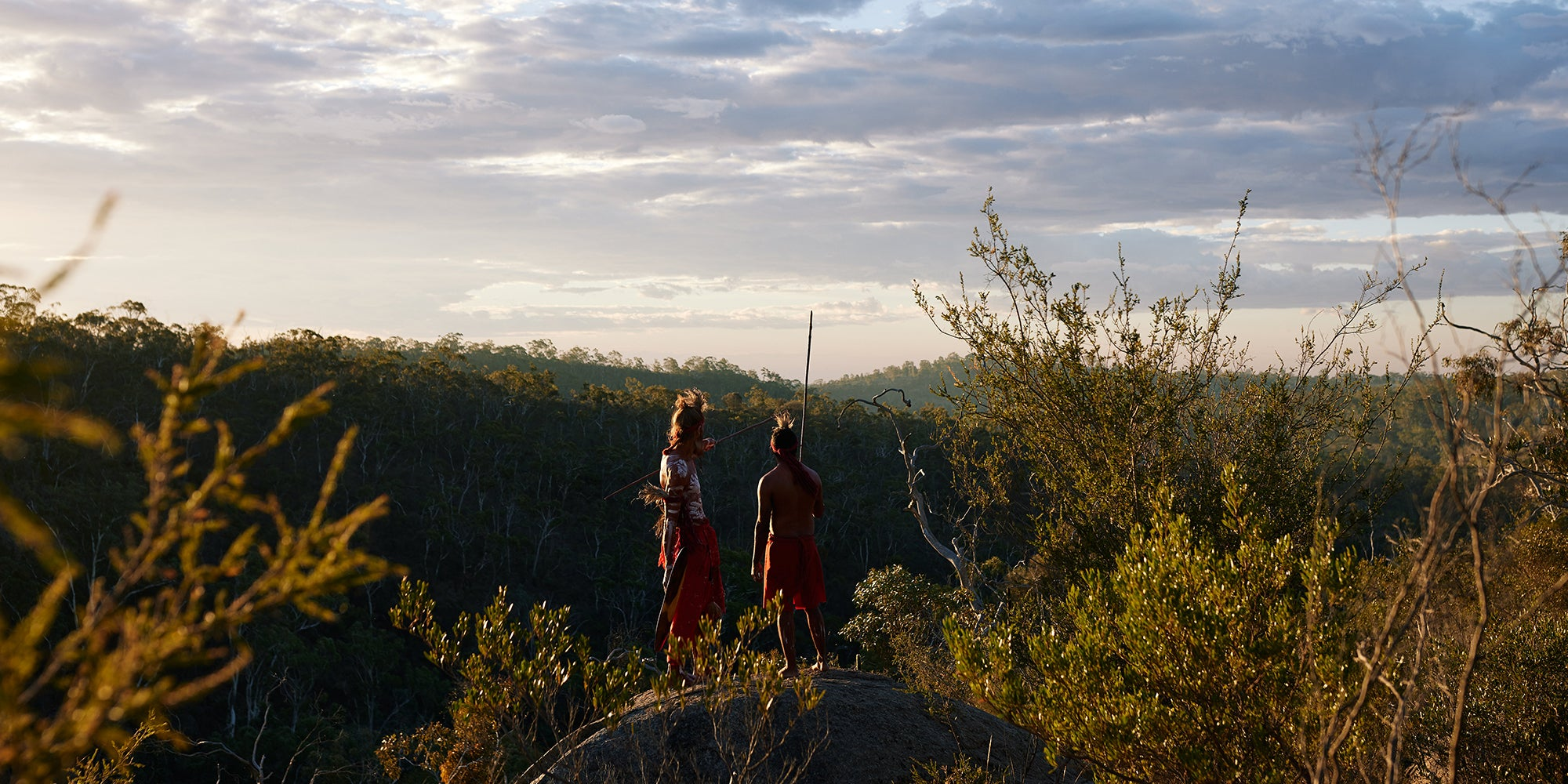 First Nations Men in traditional dress looking over land