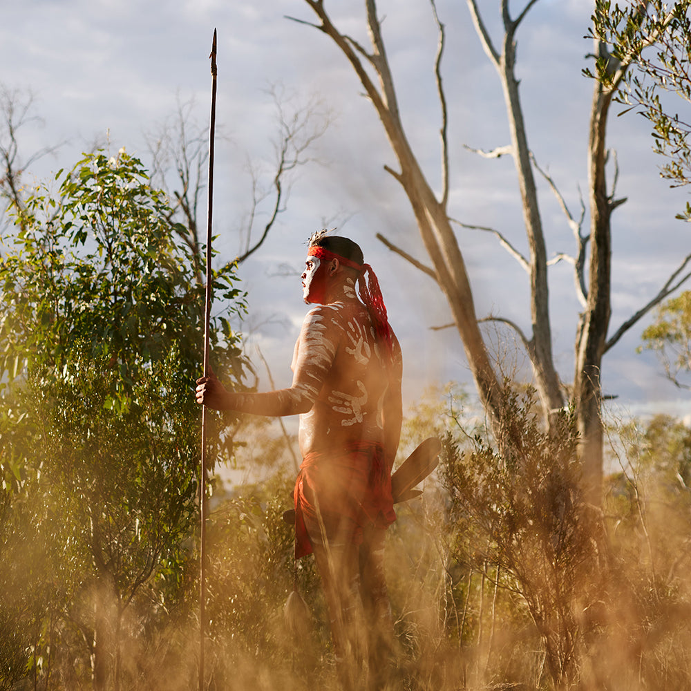 First Nations Man in traditional dress standing in bushes