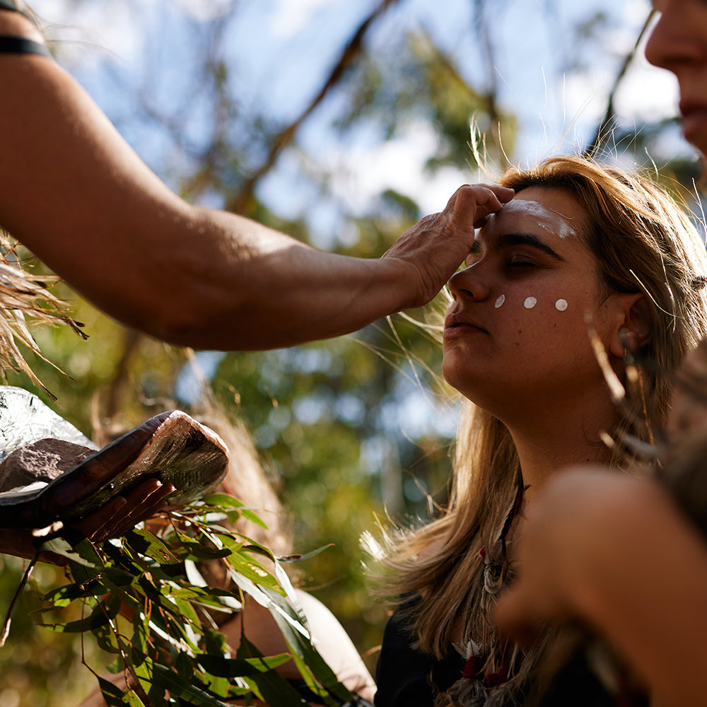 First Nations Women applying traditional face paint