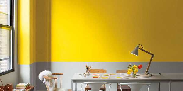 room with long desk and wall with yellow and grey horizontal split