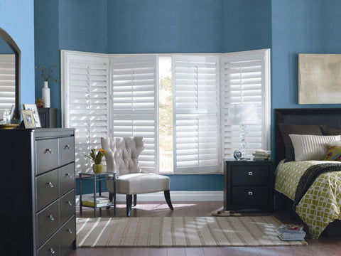 bedroom with blue walls and white shutters