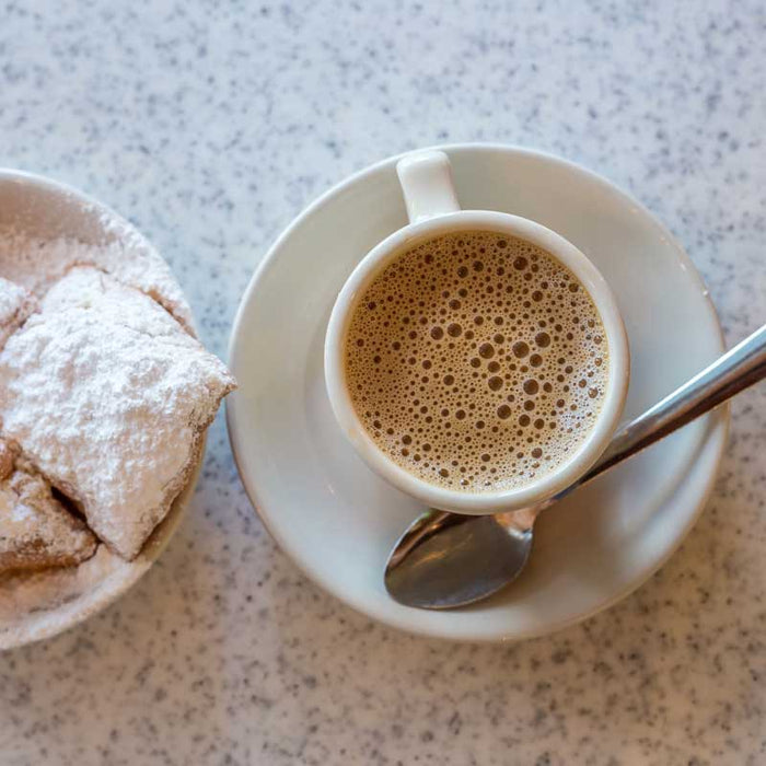 A cup of Cafe Du Monde's coffee and Chicory along with some powdered bengiets