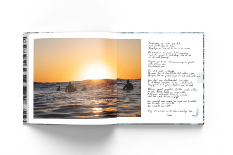 Mockup of the memorial book with the photograph of a sunset with surfers in the water.