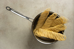 Egg tagliolini pasta noodles being boiled in a saucepan for the recipe.