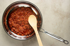 Heat up your spicy red pepper pesto sauce in a saucepan for your recipe.