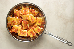 Mix the cooked paccheri pasta noodles with the spicy red pepper pesto sauce before the last touch of the recipe.