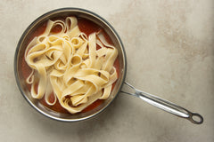 Add the pappardelle pasta noodles with the tomato sauce, minced garlic, and olive oil.