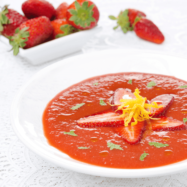 Strawberry gazpacho with decorated cheese garments and parsley.
