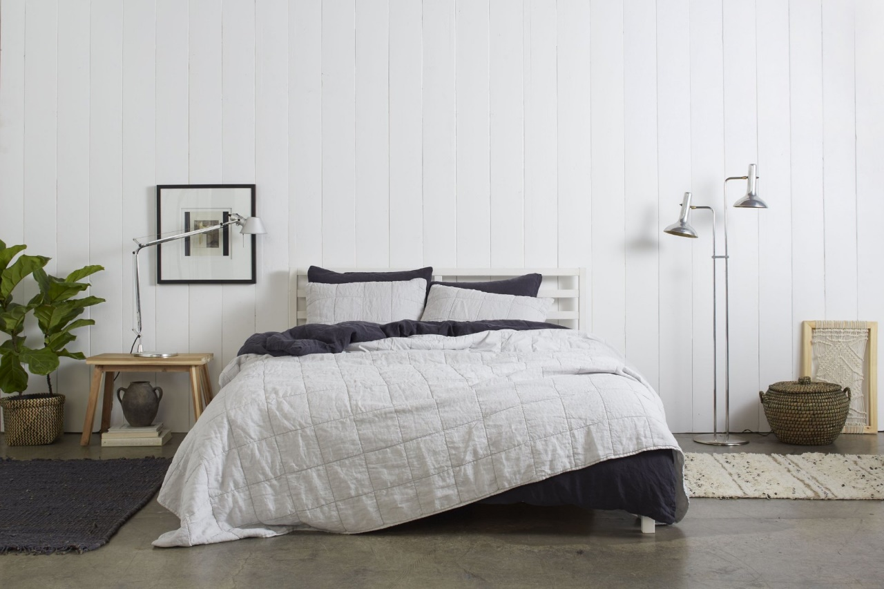 Parachute's linen box quilt in solid color layering on the top of a dark bedding piece