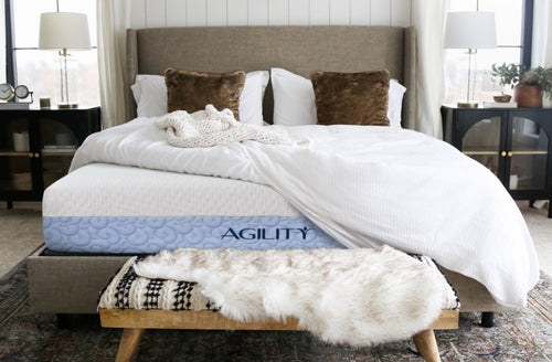 An unmade bed showing agility hybrid mattress underneath.
