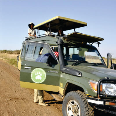 a driver-guide boarding a green 4x4 safari jeep with a Bon Voyage Safaris logo and two women sitting near pop-up rooftop at daytime in Masai Mara