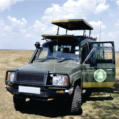 Green 4WD land cruiser safari jeep with logo of Bon Voyage Kenya Safaris and pop-up roof is parked in short grass during daytime in Masai Mara