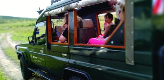 Three people in an open sided 4x4 green safari jeep during 3 days budget tours in the Masai Mara National Reserve