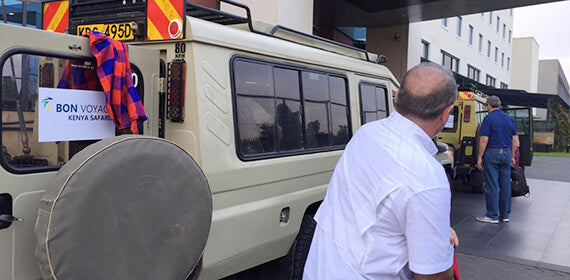 Two 4x4 safari jeeps parked near hotel in Nairobi with passengers arrange their language inside during 14-day Cheap Safari in Tanzania and Kenya