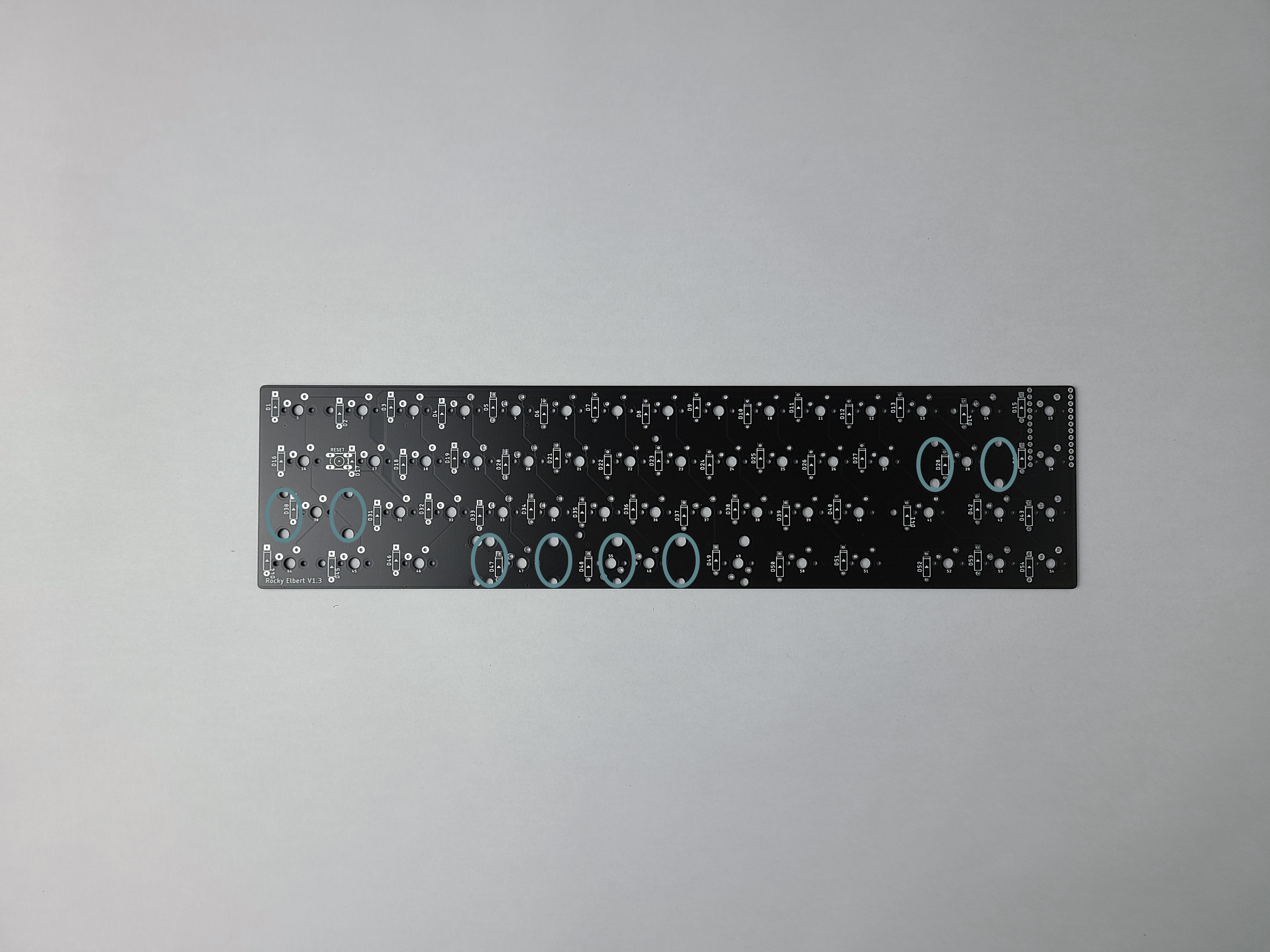 PCB with stabilizer cutouts for switches 28, 30, 47, and 48 circled