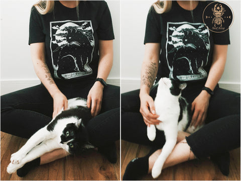 Soft goth style girl, wearing jeans and playing with her cat