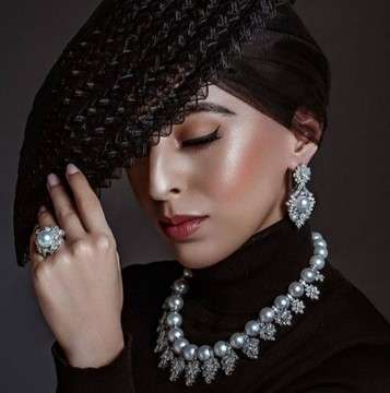 Model in black hat and dress with costume jewelry