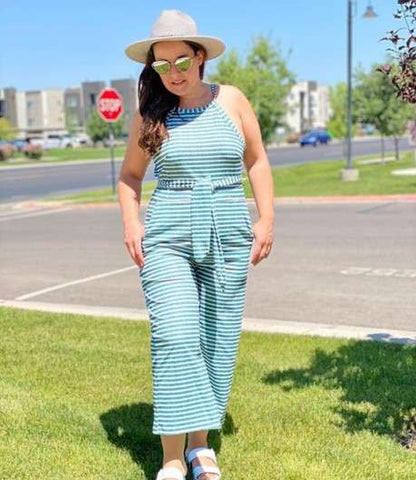 Plus size model in a light blue jumpsuit and hat