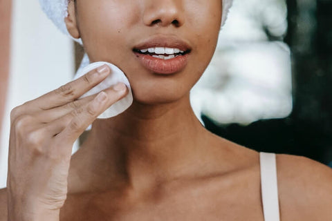 Woman applying makeup to her face using a cotton sponge