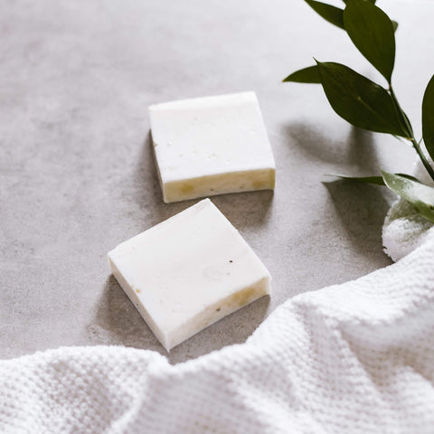 Two bars of white soap on a table with a cloth under them and a plant on the right
