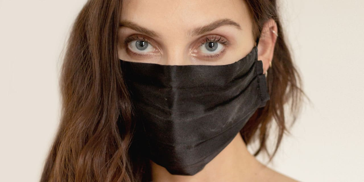 A woman stares into the camera, her face comfortably covered with an NK IMODE black silk face mask.