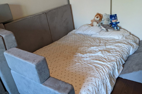 play couch pieces surround a mattress in a bedroom on the floor