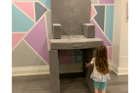 little girl builds a chair that is very tall in the air out of her play couch