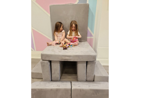 two little girls sitting on a play couch built in to a chair off the ground