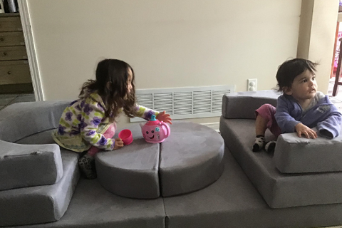 two little girls sit as restaurant booth play couch build