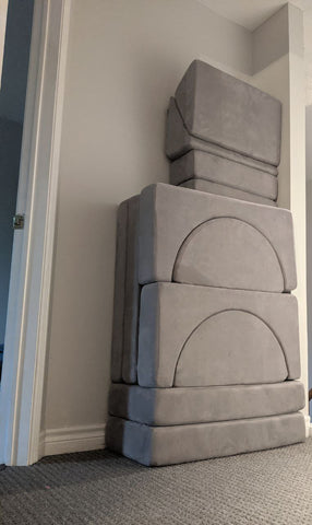 play couch pieces stacked in a hallway