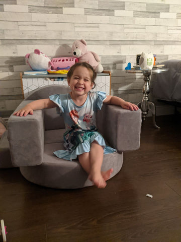 little girl sitting on a play couch in a small chair play couch build