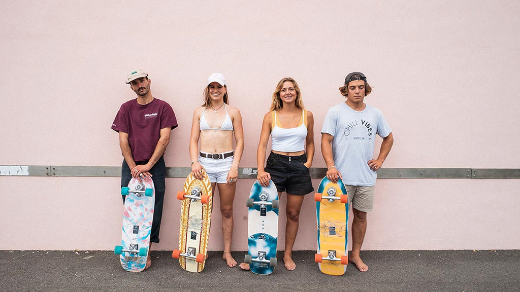 Yow surfskate team standing against pink wall holding surf skates