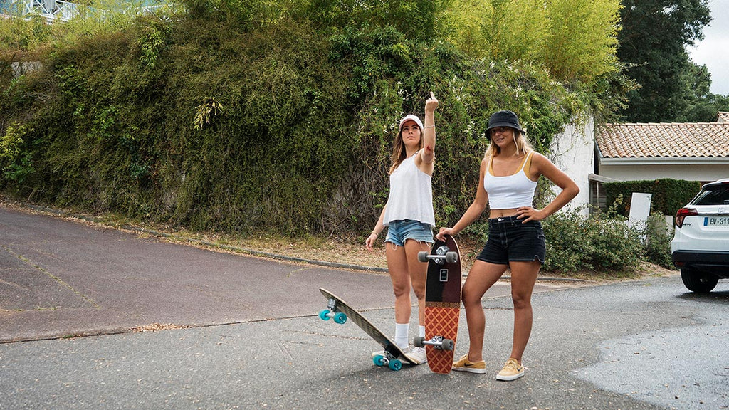 two girls holding surfskates flipping off the photographer in australia