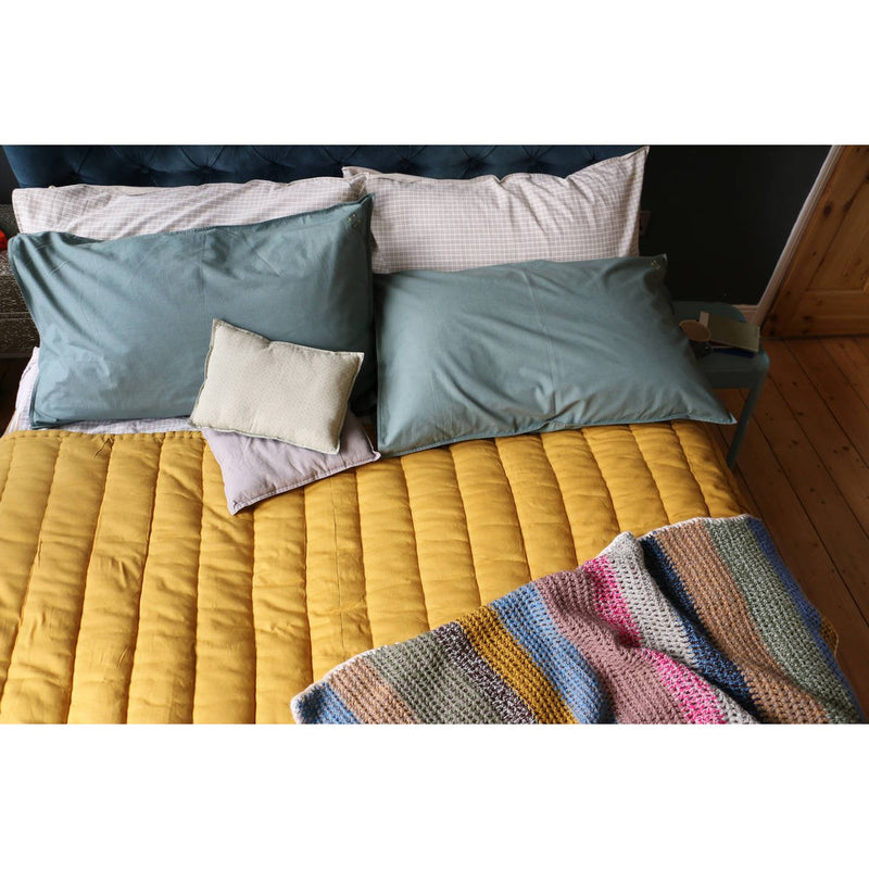 Camomile London Quilted Cotton Blanket | ochre - on bed