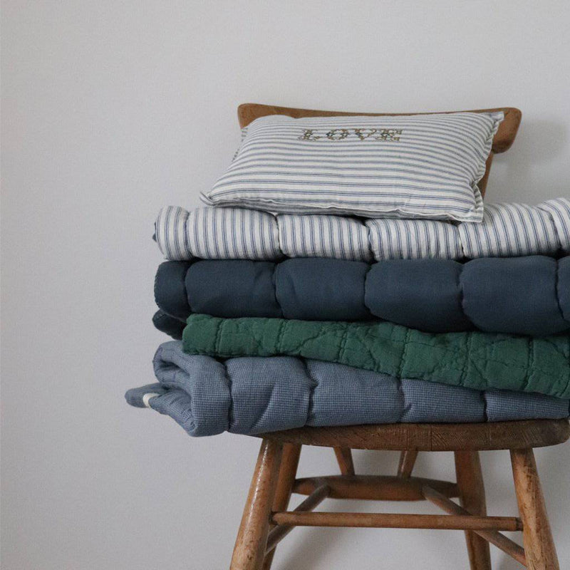 Camomile London | diamond single cotton blanket | airforce blue - pile on chair