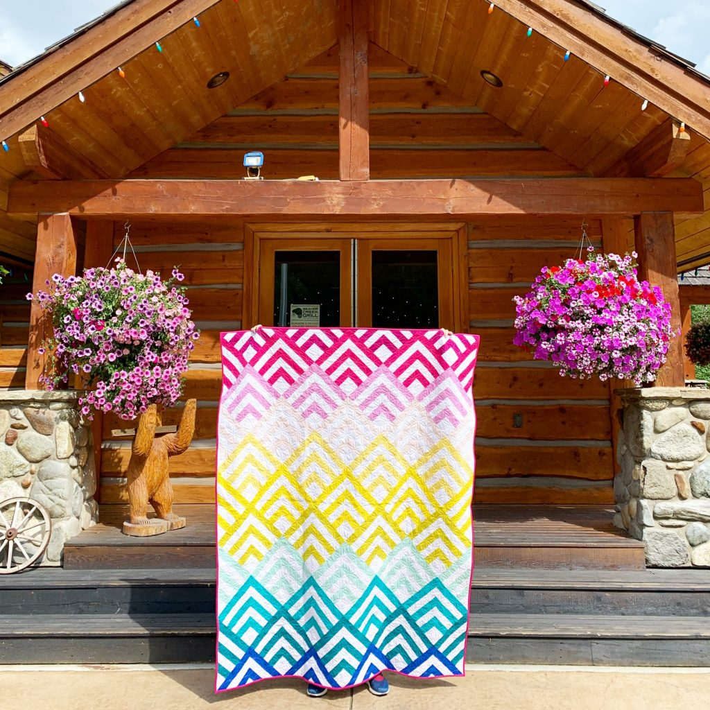 Cabin Peaks finished quilt outside a cabin