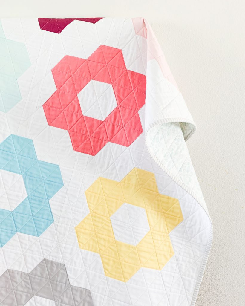 Quilting, binding, and backing details on Hexie Blooms quilt