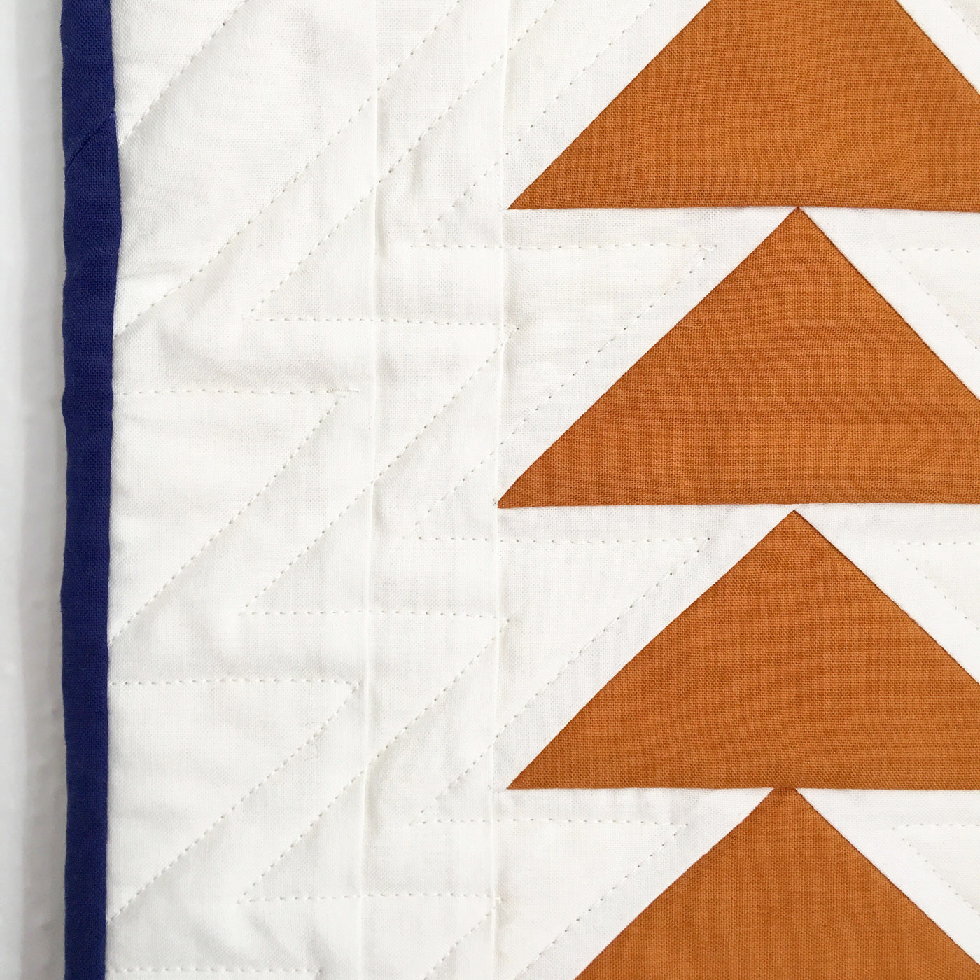 Close up of straight line quilting on a flying geese quilt