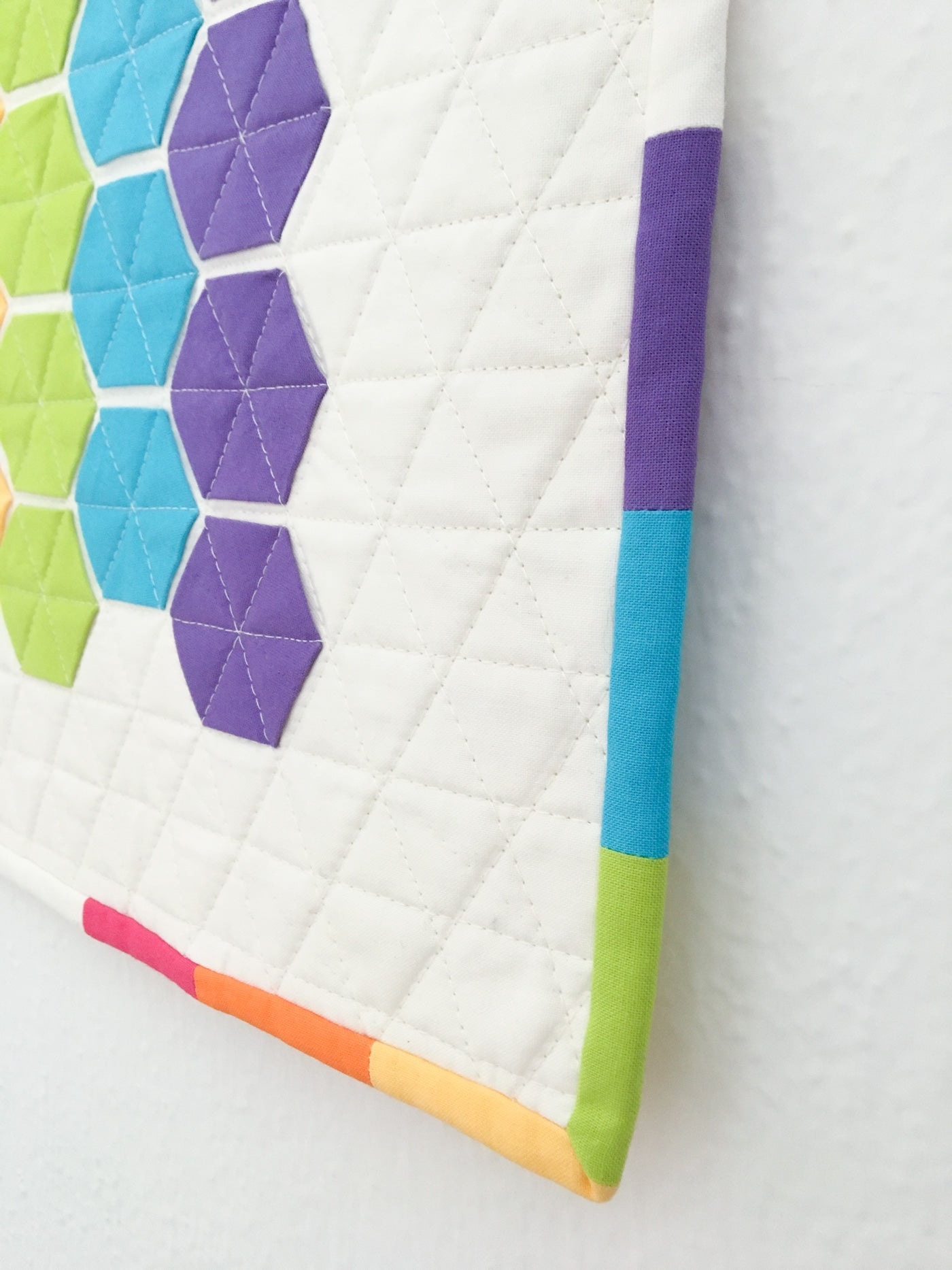 Quilt binding idea: multicolor quilt binding corner using fabric from quilt top