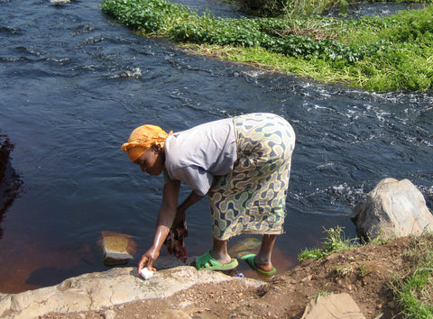 Rwandan woman doing laundry in the river