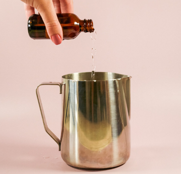 pouring fragrance oil into silver pitcher